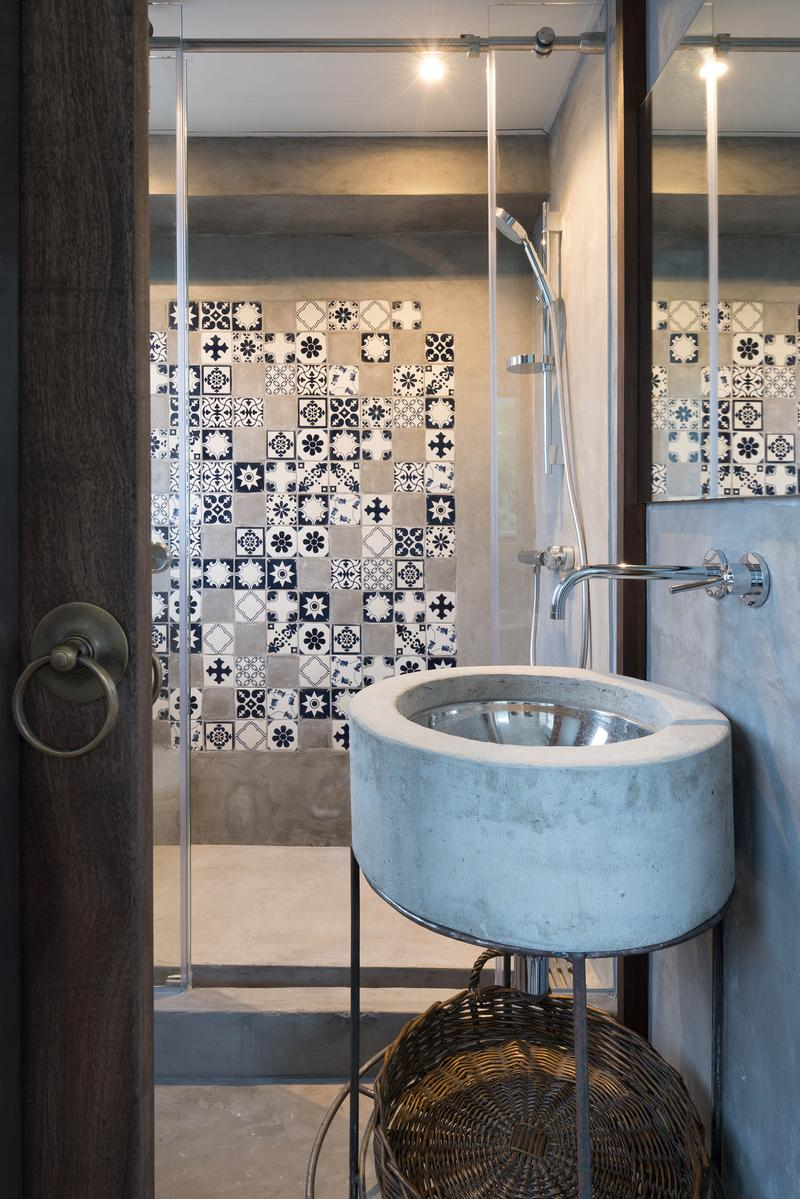 The shower space showcases an intricate display of tilework. The sink basin is encased in concrete, fitting the aesthetic of the room.