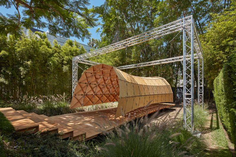 Suspended from aluminum trusses and braced with steel wires, the double-curved kinematic pavilion structure is made of hinged and stiffened wood panels. / © Benny Chan
