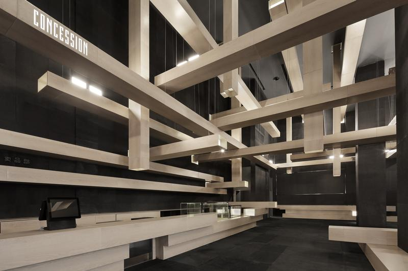 Dark boxes morph into rectangular columns that crisscross each other in the lobby ceiling, forming a dynamic ceiling feature. The angular arrangement gives a clean finish to the ceiling feature, the c