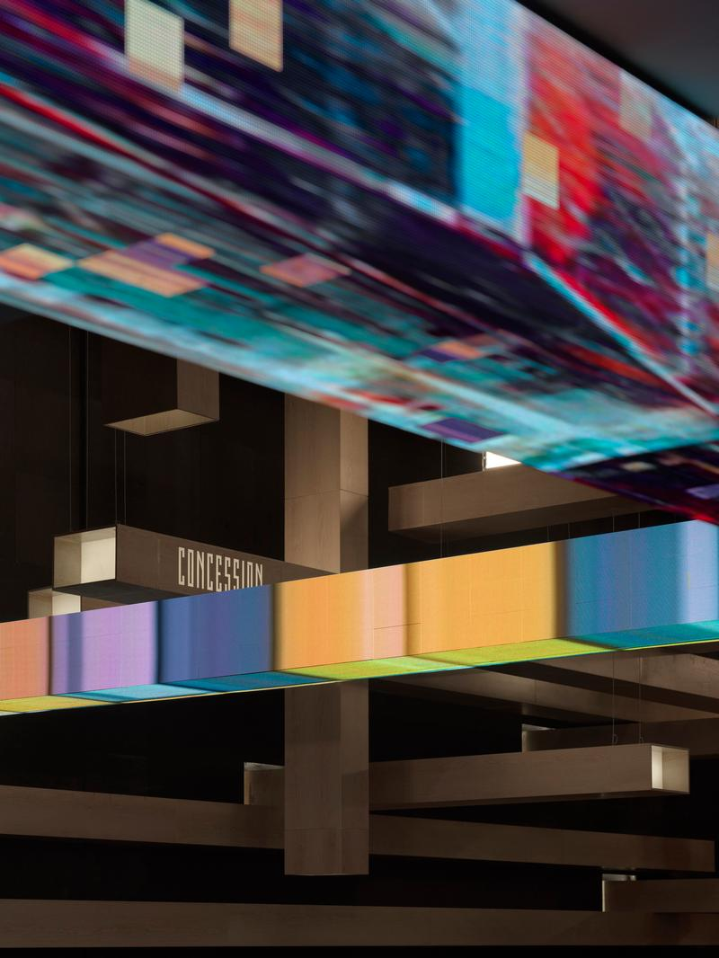 The columns are produced from aluminium panels painted with a light color wood pattern, becoming the dominant visual element with black walls and ceiling. Small televisions are installed at the end of